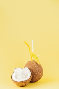 Fresh coconut cocktail with a straws on yellow background, copy space.