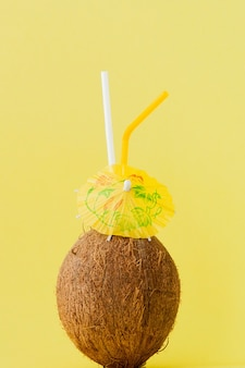 Fresh coconut cocktail with a straws on yellow