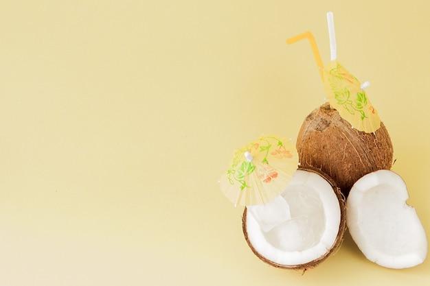 Свежие кокосовые коктейли с пластиковой соломкой на желтом фоне с копией пространства