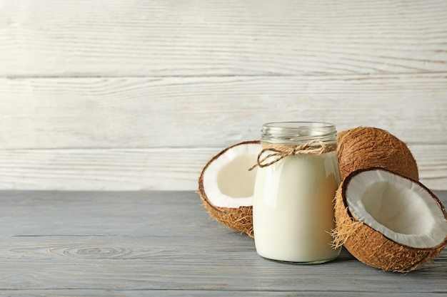 Fresh coconut and coconut milk on wooden background