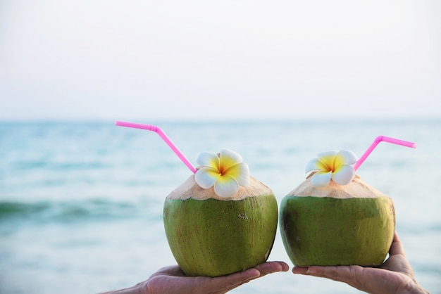 Fresh coconut in couple hands with plumeria decorated on beach with sea wave - honeymoon couple tourist with fresh fruit and sea sand sun vacation concept