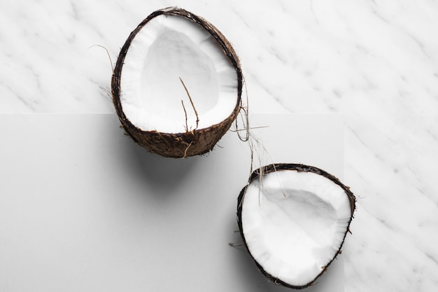 Fresh coconut cut in half on white and marble backdrop