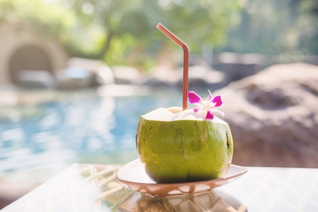 Fresh coconut juice on a wooden table