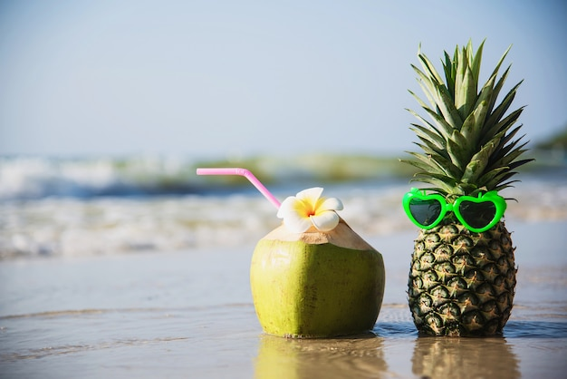Fresh coconut and pineapple put sun lovely glasses on clean sand beach with sea wave - fresh fruit with sea sand sun vacation concept