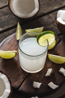 Fresh coconut water in glass cup on wooden table