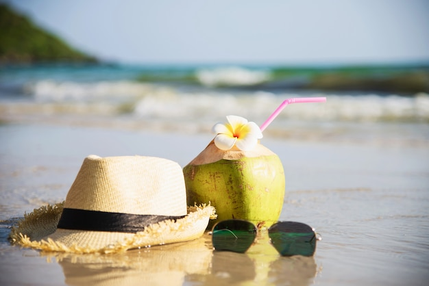 Fresh coconut with hat and sun glasses on clean sand beach with sea wave - fresh fruit with sea sand sun vacation concept