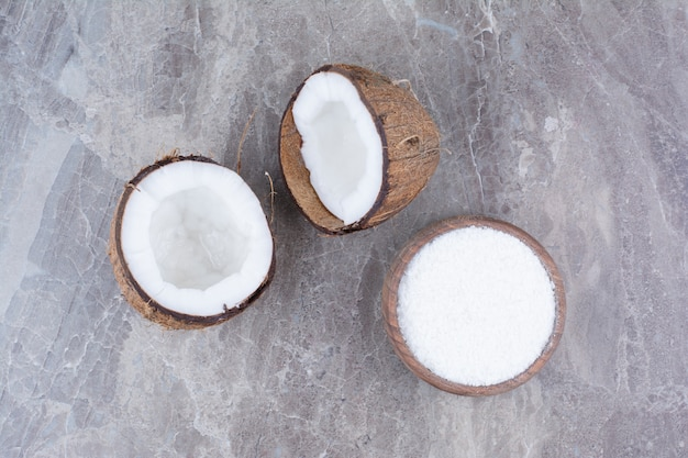 Fresh coconuts and bowl of sugar on stone surface.