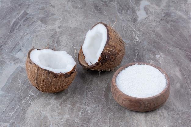 Noci di cocco fresche e ciotola di zucchero sulla superficie della pietra.