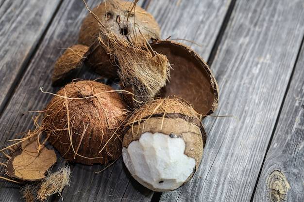 Fresh coconuts broken on wooden wall