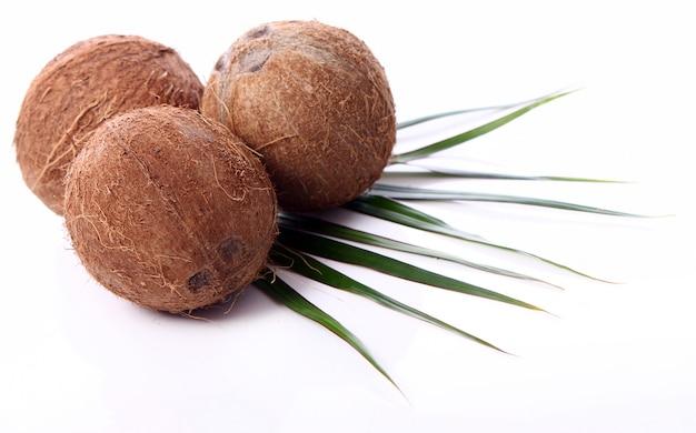 Свежие кокосы на белой поверхности
