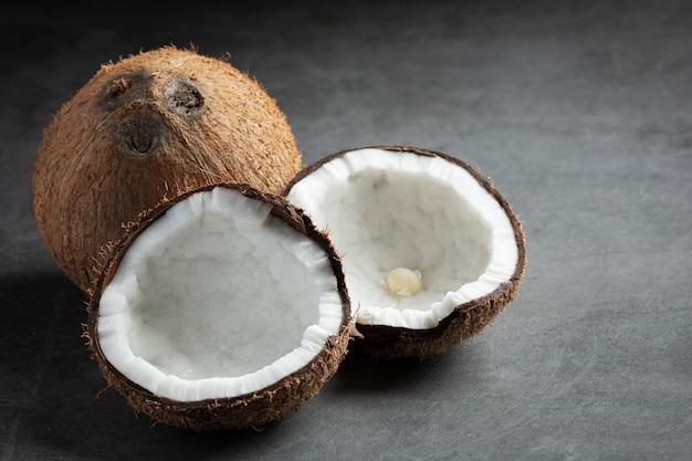 Noci di cocco fresche messe su sfondo scuro
