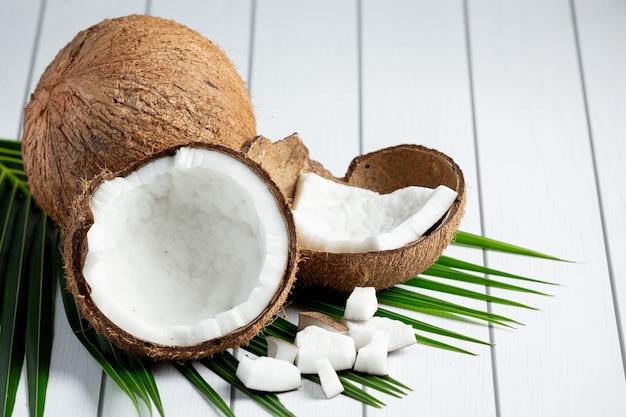 Noci di cocco fresche messe su fondo di legno bianco