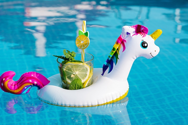 Fresh coctail mojito on inflatable white unicorn toy at swimming pool. vacation concept.