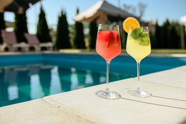 Свежие коктейли у бассейна на открытом воздухе, никого. летние каникулы или каникулы. напитки в стаканах у бассейна в жаркий солнечный день