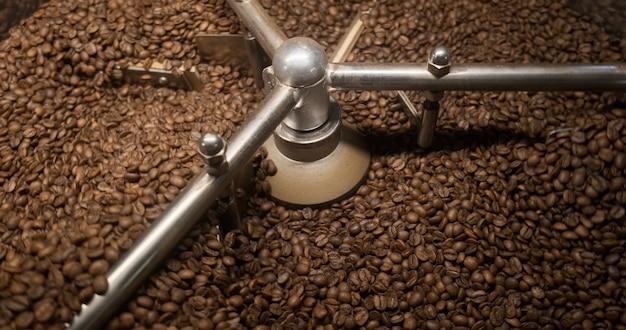 신선한 커피 콩 갓 볶은 아라비카 커피 콩이 회전에 떨어지는