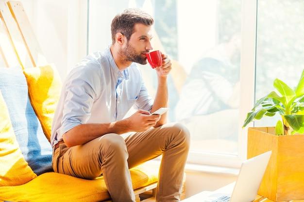 新鮮なアイデアのための淹れたてのコーヒー。携帯電話を持って、オフィスの休憩所に座ってコーヒーを飲むハンサムな若い男