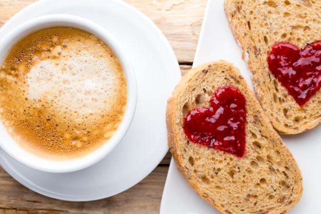 新鮮なコーヒー。ジャムハート形のパンの穀物のスライス。