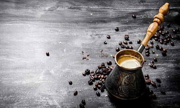 Свежий кофейник с зернами вокруг на черной доске.
