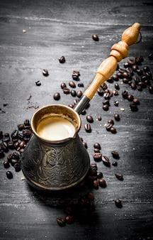Fresh coffee pot with grains around.