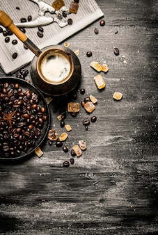 Fresh coffee pot with the newspaper and roasted coffee beans on wooden table.
