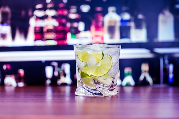 Fresh cold cocktail with lime on bar background
