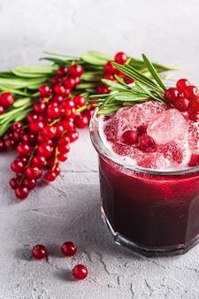 ガラスの新鮮な冷たいフルーツカクテル、ローズマリーの葉でさわやかな夏の赤スグリの果実の飲み物