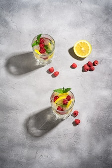 Напиток из свежей холодной ледяной воды с лимоном, плодами малины и листом мяты