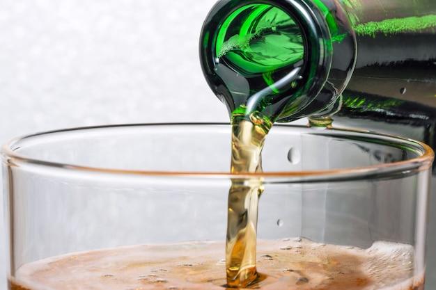 신선한 차가운 라이트 맥주가 녹색 병에서 유리 클로즈업 매크로 사진에 부어집니다.