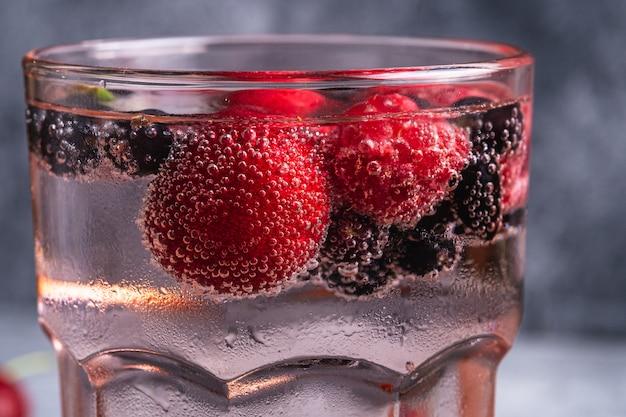 赤いファセットグラスにチェリー、ラズベリー、スグリの果実が入った新鮮な冷たい炭酸水ドリンク
