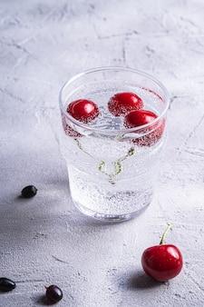 新鮮な冷たい炭酸水ドリンク、チェリー、ラズベリー、スグリの果実、石のコンクリート表面、夏のダイエット飲料、アングルビューマクロの透明なガラス