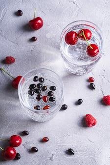 石のコンクリートの背景、夏のダイエット飲料、角度のビューの2つの透明なガラスにチェリー、ラズベリー、スグリの果実と新鮮な冷たい炭酸水ドリンク