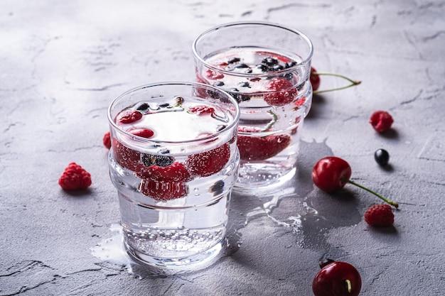 石のコンクリートの表面、夏のダイエット飲料、ビューマクロで2つの透明なガラスのチェリー、ラズベリー、スグリの果実と新鮮な冷たい炭酸水ドリンク