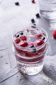 2つの透明なガラスにチェリー、ラズベリー、スグリの果実が入った冷たいスパークリングウォータードリンク