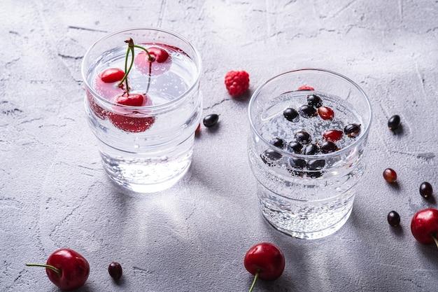2つの透明なグラスにチェリー、ラズベリー、スグリの果実が入った新鮮な冷たい炭酸水ドリンク