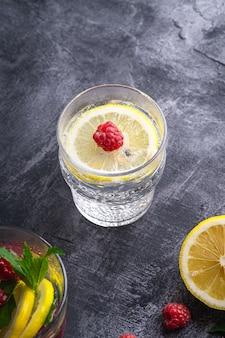 レモン、ラズベリーのフルーツ、ガラスの石の表面に新鮮な冷たい炭酸水ドリンク