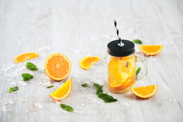 Fresh cold summer lemonade from citrus and sparkling water in rustic jar with stripe straw isolated on wooden table.
