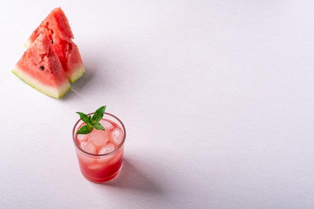 Свежий холодный арбузный сок с кубиками льда и зеленым листом мяты в стакане пить рядом с двумя ломтиками арбуза
