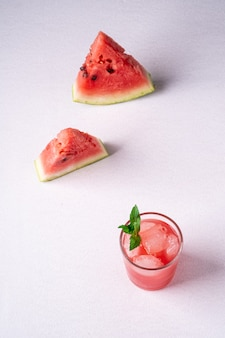 Fresh cold watermelon juice with ice cubes and green mint leaf in glass drink close to two slices of watermelon