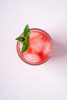 Fresh cold watermelon juice with ice cubes and green mint leaf in glass drink on white wall, top view