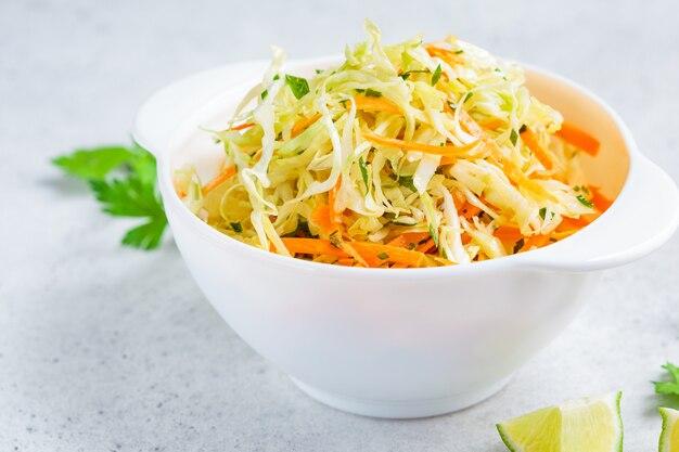 キャベツとニンジンの白いボウルの新鮮なコールスローサラダ。
