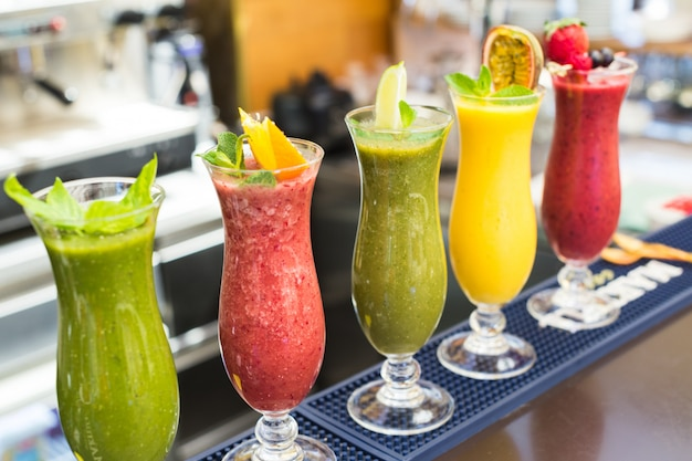 Fresh color juices smoothie violet green yellow orange red tropical fruits