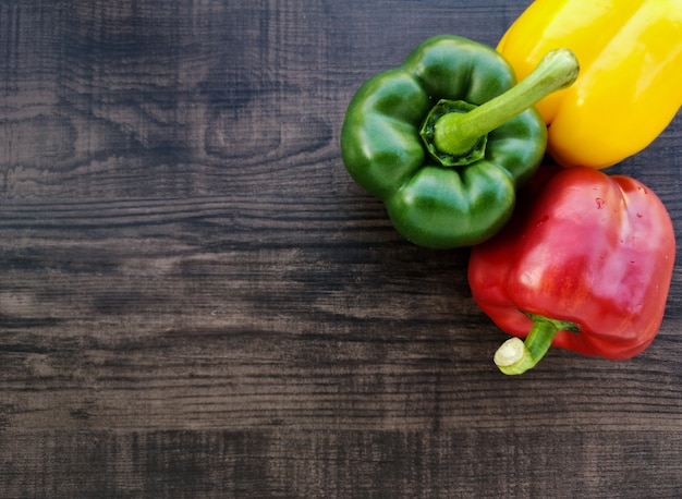 Fresh colorful bell peppers. wood background