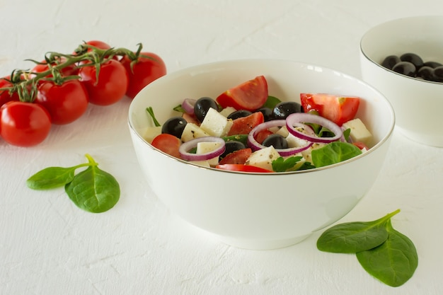 Свежий красочный греческий салат или хориатики с овощами подается с сыром фета в белой миске.