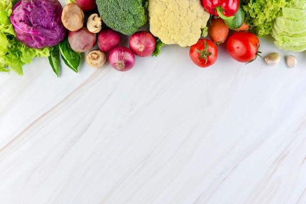 大理石のカウンタートップの背景に新鮮なカラフルな健康野菜 Premium写真