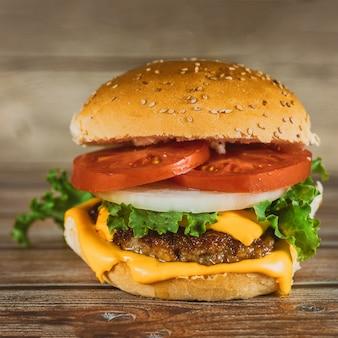 Fresh colorful homemade hamburger on wooden table.