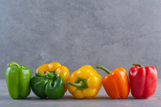 Fresh colorful organic peppers placed on stone surface