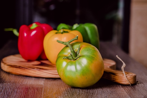 Fresh colorful peppers and eggplant on a cutting wood