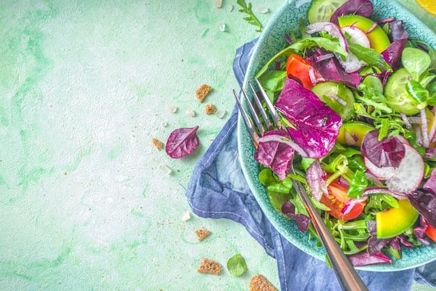 新鮮なカラフルな春のサラダ-アボカド、新鮮な野菜、サラダの葉とフェタチーズ、薄緑色のコンクリートの背景