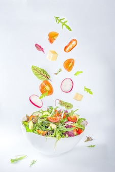 Fresh colorful spring salad - avocado, tomato, lettuce, onion,  radish, cucumber, cheese. in white bowl on white background copy space, with levitation ingredients