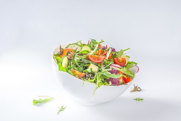 Fresh colorful spring salad - avocado, tomato, lettuce, onion,  radish, cucumber, cheese. in white bowl on white background copy space